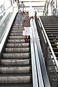 Boy standing on escalator while his brother walking away - FSF00952