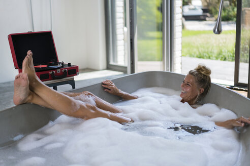 Mature woman taking bubble bath, listening music from analogue record player - RIBF00675