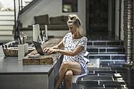Woman sitting in kitchen, using laptop - RIBF00678