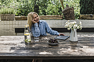 Mature woman sitting on terrace, enjoying summer - RIBF00681