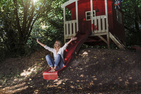 Mature woman sitting on slide in front of garden shed in the woods - RIBF00684