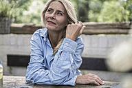 Mature woman sitting on terrace, thinking - RIBF00729