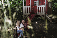 Happy couple sitting on slide of garden shed in the woods - RIBF00747