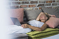 Mature woman lying on couch, usine laptop - RIBF00753