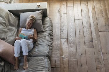 Woman relaxing on couch, reading book - RIBF00756
