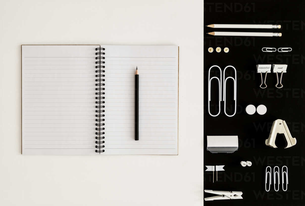 White office utensils on black background and notepad and pencil on whilte background - MELF00186 - Melanie Kintz/Westend61
