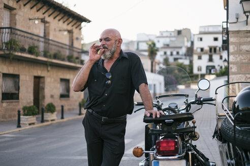 Spain, Jaen, mature man smoking next to motorcycle with a sidecar - JASF01814