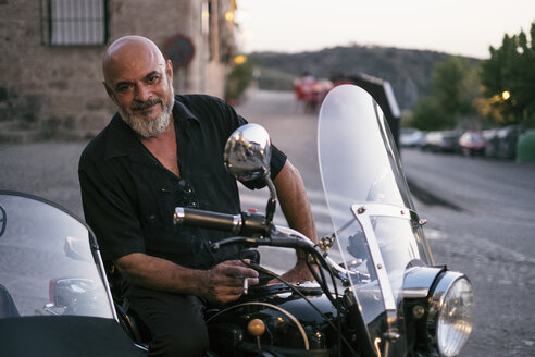 Spain, Jaen, mature man posing on his motorcycle with a sidecar while smoking - JASF01817