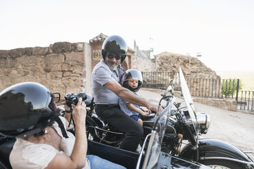 Spain, Jaen, woman taking picture of grandfather and grandson on motorcycle with a sidecar - JASF01826