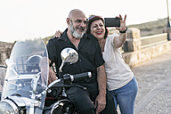 Spain, Jaen, mature couple with motorcycle with a sidecar taking a selfie - JASF01835