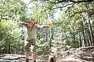 Man shooting with bow and arrow in the forest - MFRF00983