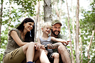 Happy family with son sitting in forest - MFRF00992