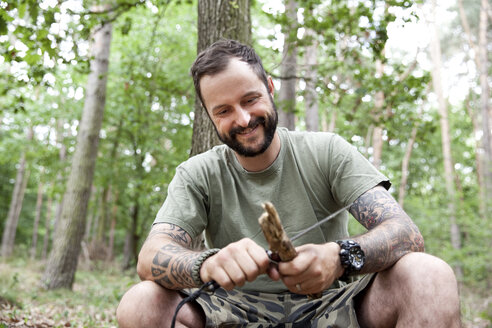 Smiling man carving in the forest - MFRF00998