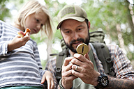 Father showing compass to daughter in forest - MFRF01013