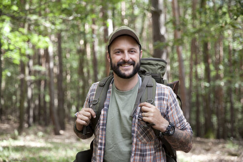 Portrait of smiling man with backpack on a hiking trip in forest - MFRF01016
