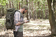 Man with backpack on a hiking trip in forest using cell phone - MFRF01019