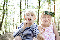 Boy and girl in forest eating heart-shaped pretzel pastry - MFRF01028