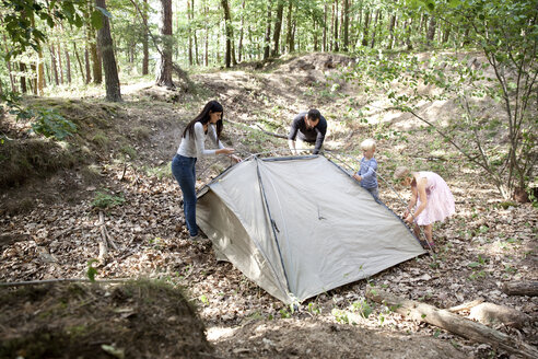Family in forest building up tent together - MFRF01031