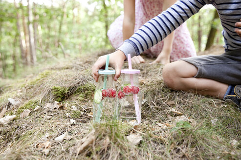 Boy reaching for glass of infused water with cucumber slices and raspberries in forest - MFRF01034
