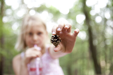 Close-up of girl holding pine cone in forest - MFRF01037