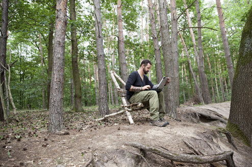 Man sitting on self-made wooden chair in forest using laptop - MFRF01049