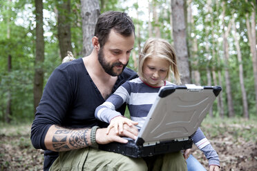 Father and daughter in forest using laptop - MFRF01052