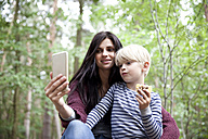 Mother and son taking a selfie in forest - MFRF01055