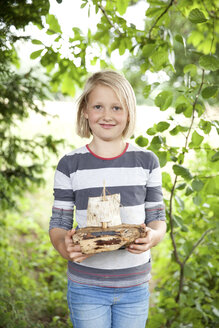 Portrait of smiling girl holding carved wooden boat in forest - MFRF01058