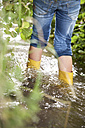 Girl with rubber boots wading in brook - MFRF01061