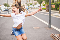 Screaming blond girl jumping in the air - SIPF01695