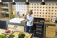 Smiling mature woman holding an apple in kitchen - RBF05844
