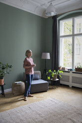 Mature woman at home looking out of window - RBF05847