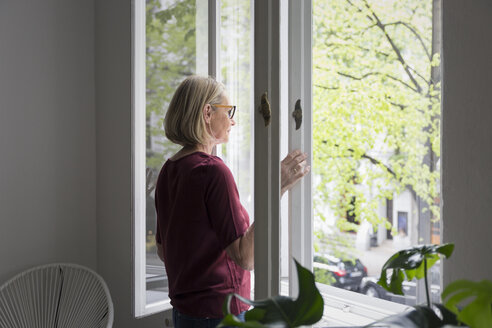 Mature woman at home opening the window - RBF05850