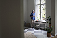 Mature man at home looking out of window - RBF05856