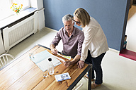 Mature couple with documents and tablet at home - RBF05859