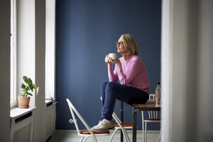 Mature woman at home with cup of coffee looking out of window - RBF05871