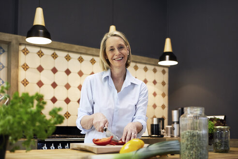 Portrait of smiling mature woman chopping bell pepper in kitchen - RBF05877