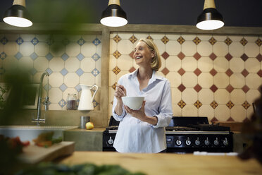 Happy mature woman holding bowl in kitchen - RBF05880