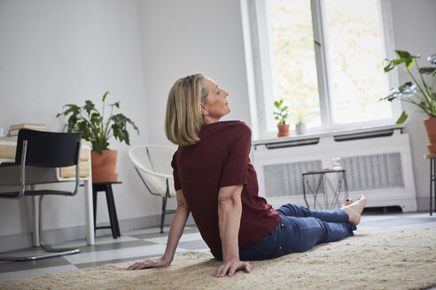 Relaxed mature woman sitting on the floor at home - RBF05892