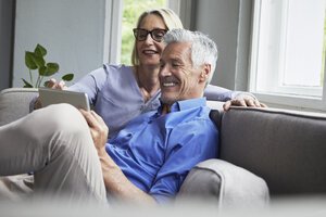 Happy mature couple sitting on couch at home sharing tablet - RBF05901