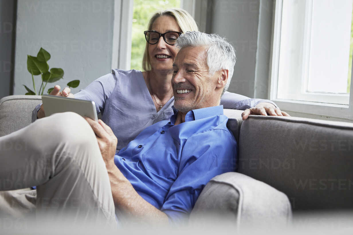 Happy mature couple sitting on couch at home sharing tablet - RBF05901 - Rainer Berg/Westend61
