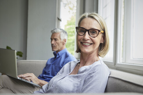 Portrait of smiling mature woman on couch with man in background using tablet - RBF05904