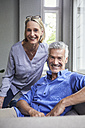 Portrait of smiling mature couple on couch at home - RBF05907