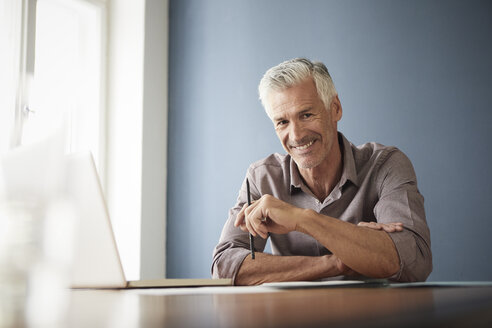 Portrait of confident mature man with laptop and documents at home - RBF05922