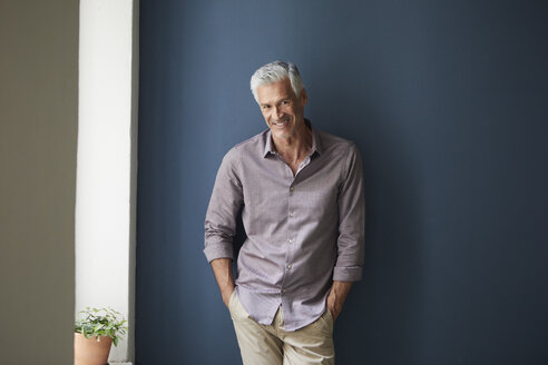 Portrait of confident mature man at home leaning against blue wall - RBF05925