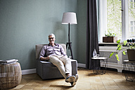 Portrait of smiling mature man sitting on armchair at home - RBF05934