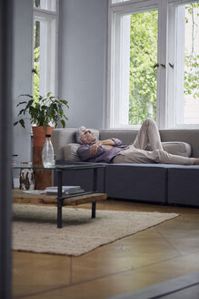 Mature man sleeping on couch at home - RBF05940