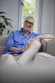 Portrait of smiling mature man sitting on couch at home - RBF05946