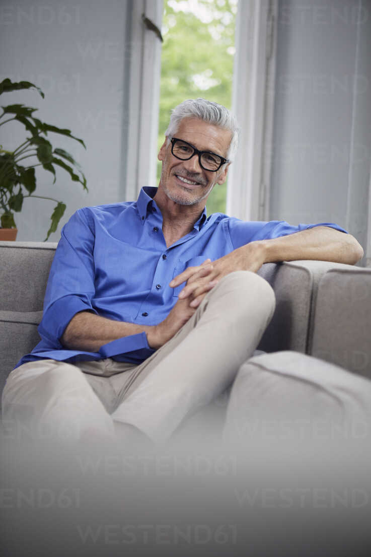 Portrait of smiling mature man sitting on couch at home - RBF05946 - Rainer Berg/Westend61