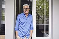 Portrait of smiling mature man leaning against balcony door - RBF05952